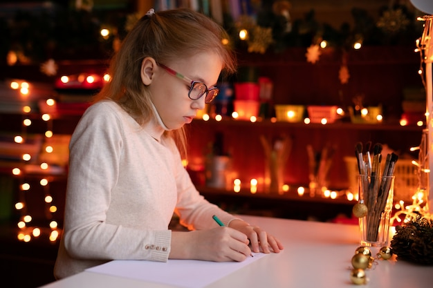 Blonde child girl with big pink ans black glasses writing letter to the santa claus