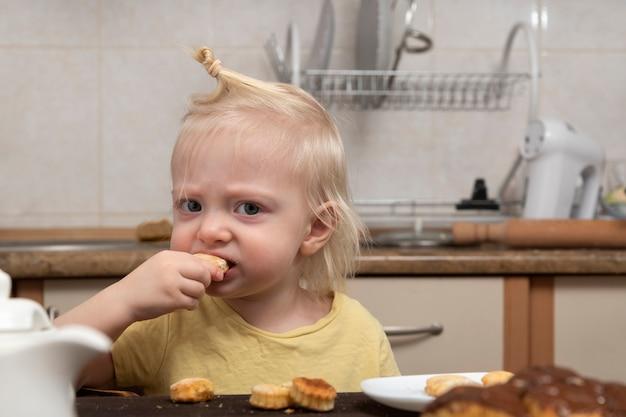 금발 아이가 부엌에서 쿠키를 먹고있다