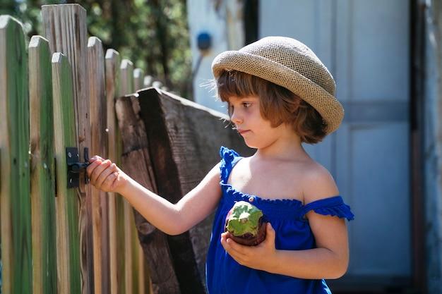 果樹園のフェンスを開こうとすると、夏には籐の帽子の金髪の子