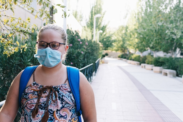 Blonde chubby girl with glasses, a blue backpack and face mask on her way to school