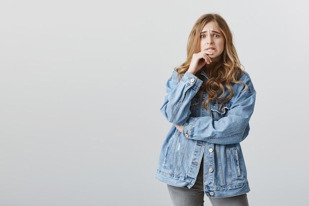 Блондинка студентка смотрит с паникой, кусает палец и нервничает