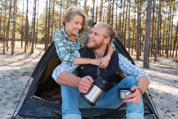 Blonde couple sitting in front of tent and hugging each other