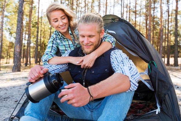Блондинка пара сидит перед палаткой и пьет кофе