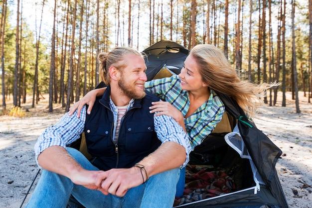 Блондинка пара сидит перед палаткой