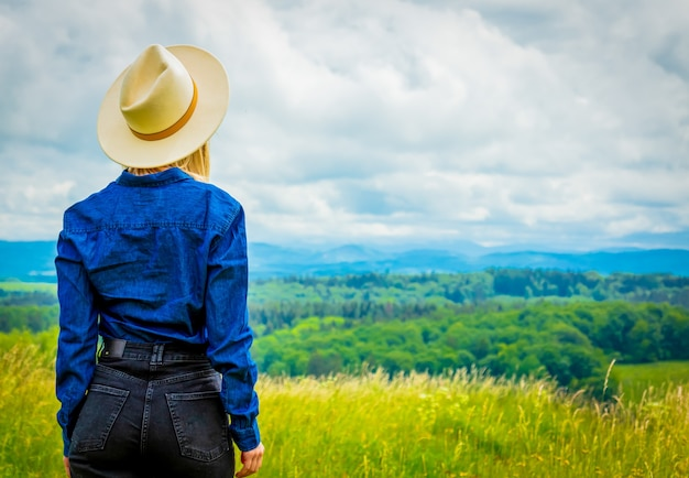 Blonde cowgirl in hat at meadow with mountains behind