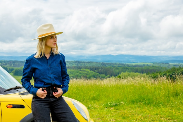 Blonde cowgirl in hat near a car at meadow with mountains