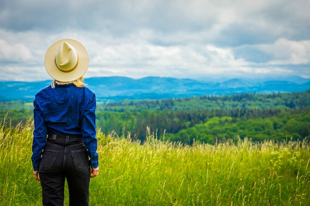 Blonde cowgirl woman in hat at meadow with mountains behind