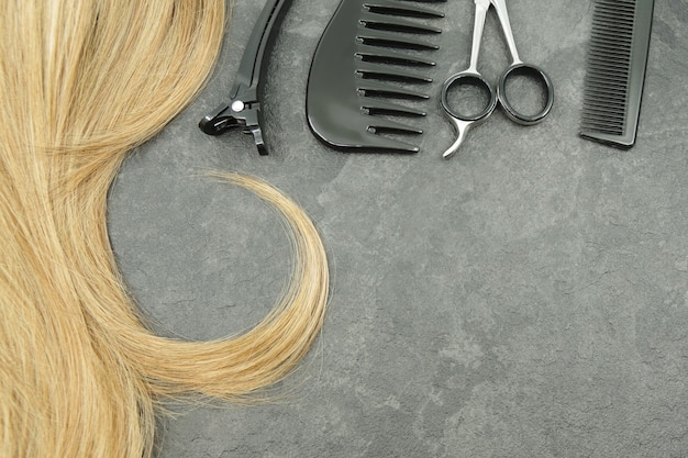 Blonde curl of hair and hairdresser set isolated on grey