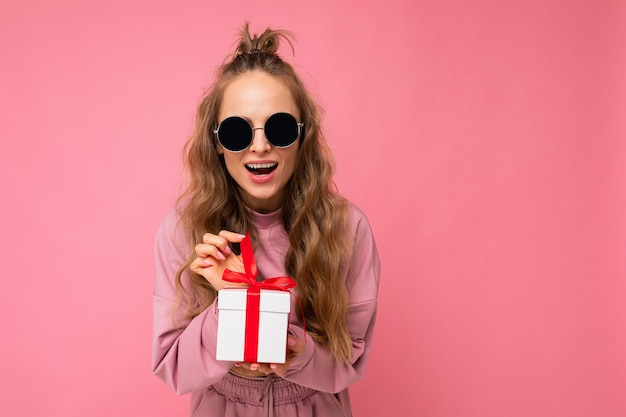 Blonde curly female person isolated on pink background wall wearing