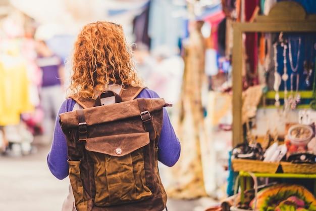 Путешественник-путешественница со светлыми вьющимися волосами, рассматриваемый сзади на бывшем в употреблении рынке, наслаждаясь покупками и альтернативным отдыхом