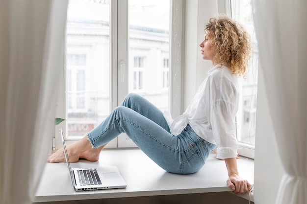 Blonde curly-haired woman relaxing at home near the window