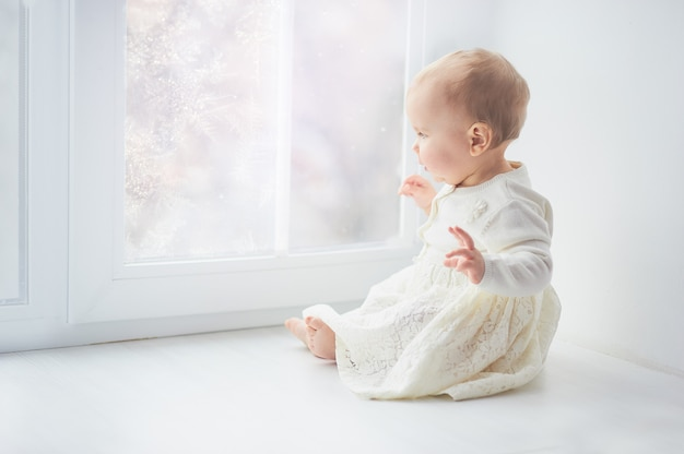 Blonde curly toddler baby girl looking through a window.