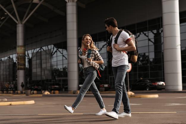 Кудрявая блондинка в джинсовых брюках и клетчатой рубашке разговаривает с брюнетом в джинсах и белой футболке