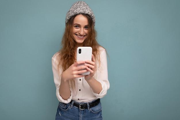캐주얼 흰색 셔츠와 파란색 배경 벽 위에 절연 회색 모자를 쓰고 금발 곱슬 여자