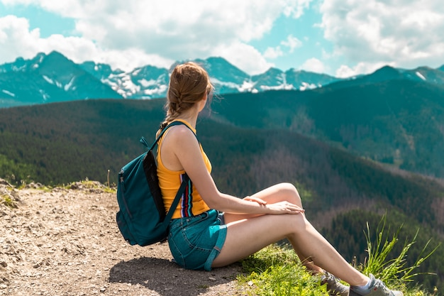Blonde cute girl with a backpack and glasses sits on a mountain and enjoys the beautiful hills of the mountains on a sunny day.