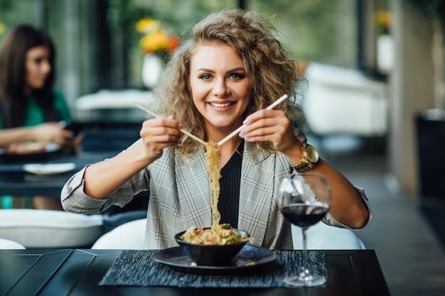 船内のレストランで箸を持った金髪のかわいい女の子。女の子はご飯とサーモンを試してみます。女の子は電化製品を食べます。仕事帰りのジャケットを着た女の子が食べる。
