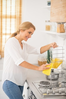 Blonde cute housewife cleaning a stove in the kitchen