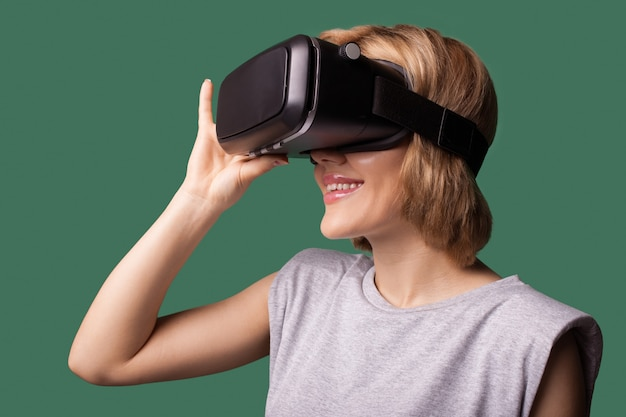 Blonde cute lady using vr headset and smile on a green  wall