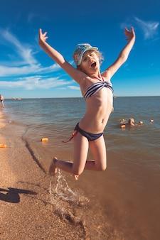 休暇中に海で楽しんで楽しい時間を過ごしている金髪のかわいい7歳の女の子。