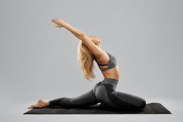 Блондинка милая молодая женщина делает упражнения йоги