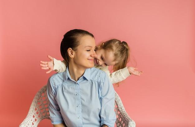 분홍색 벽에 그녀의 엄마와 함께 재미 금발 딸