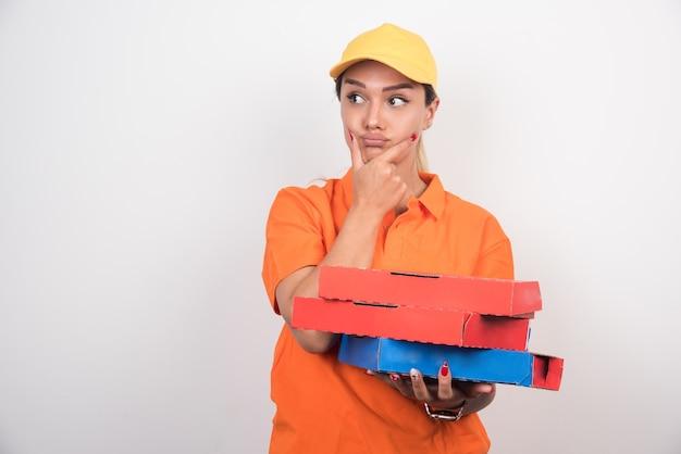Блондинка доставка женщина держит коробки для пиццы на белом пространстве, думая о чем-то