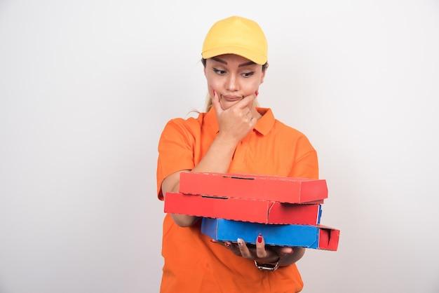 Блондинка женщина доставки, держащая коробки для пиццы, думая о чем-то.