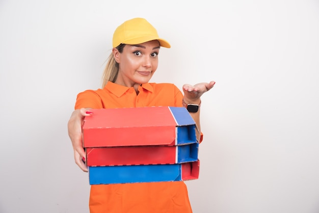 Blonde delivery woman holding pizza boxes on white space