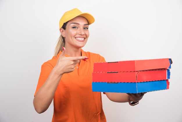 Blonde delivery woman holding pizza pointing at them on white space
