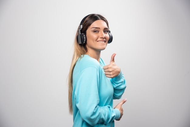 ヘッドフォンで音楽を聴いて楽しんでいる金髪のdjの女の子