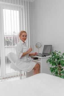 Блондинка врач в кабинете врача улыбается.