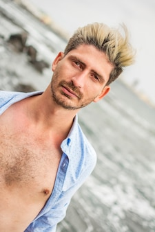 Blonde and elegant man, with his button-down shirt open and the sea in the background.