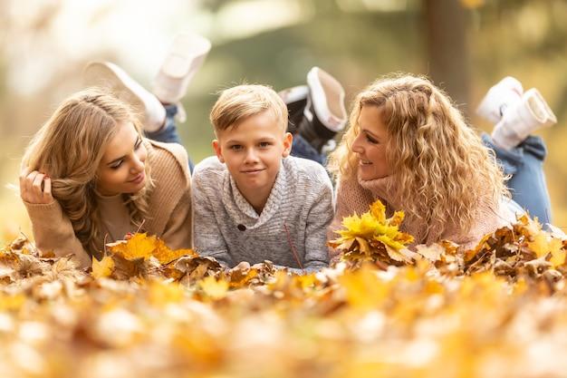母、10代の少女と少年の金髪の家族は、一緒に楽しい時間を楽しんで葉に横になります。