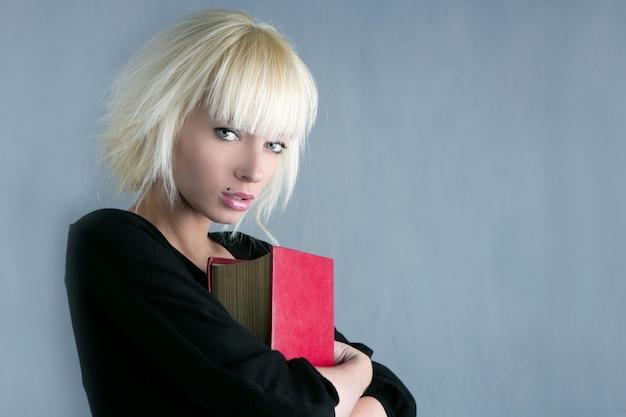 赤い本を保持している金髪のファッション学生