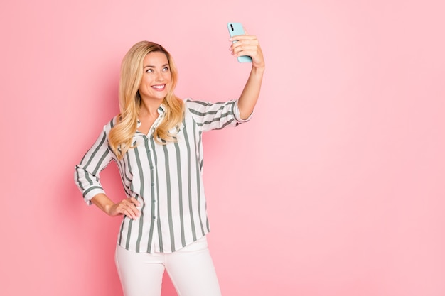 Blonde fashionable lady posing against the pink wall
