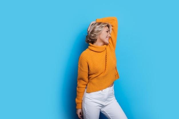 따뜻한 스웨터에 금발 유행 여자는 여유 공간이있는 파란색 벽에 포즈를 취하는 동안 웃고 있습니다.