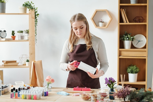 Blonde female in apron putting handmade soap bar into paper packet to give it to someone as gift for holiday