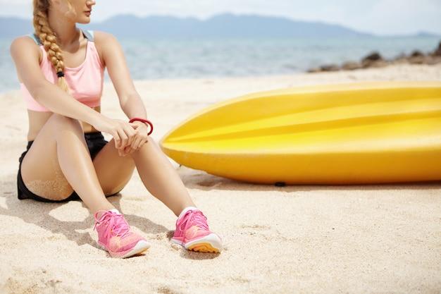 Atleta femminile biondo con la treccia lunga che riposa sulla spiaggia dopo l'esecuzione dell'allenamento, tenendo le mani sulle sue ginocchia e distogliendo lo sguardo, vista sul mare