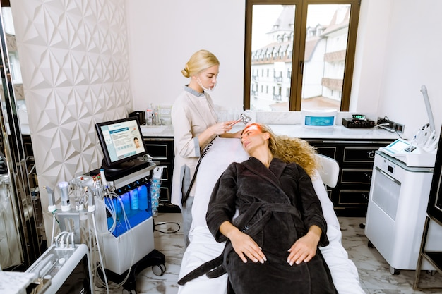 Blonde female beautician doctor applying red led light therapy to female client in cosmetology clinic, facial photo therapy.