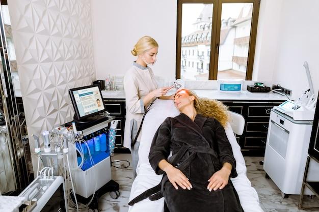 금발 여성 미용사 미용 클리닉, 얼굴 사진 치료에 여성 고객에게 빨간 led 빛 치료를 적용하는 의사.