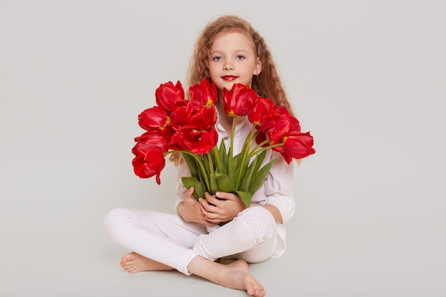 Blonde female child sitting on floor with crossed legs and holding bouquet with red tulips, looking at front, has pleasant gift