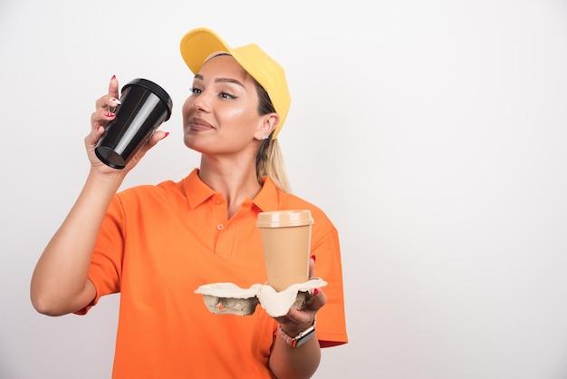 Corriere femminile biondo che beve tazza di caffè sulla parete bianca.