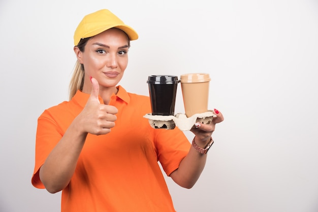 Corriere femminile biondo che tiene due tazze di caffè e che fa i pollici aumenta il segno sulla parete bianca.