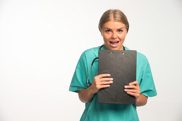 Medico femminile biondo in uniforme blu che tiene un libro di ricevute e sembra eccitato.
