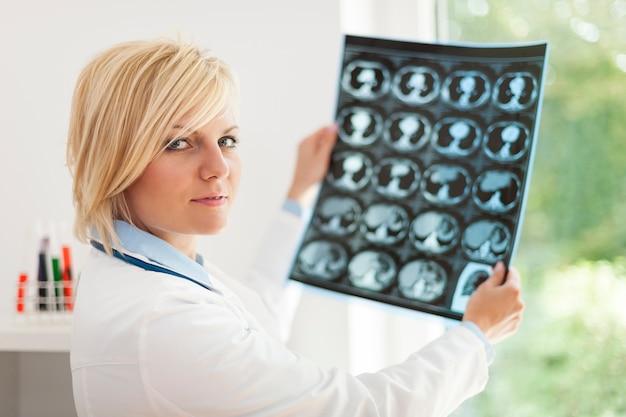 Блондинка женщина-врач держит рентгеновское изображение
