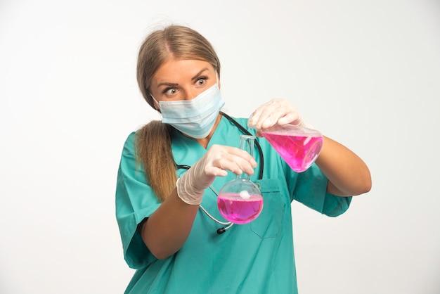 얼굴 마스크를 착용하고 한 플라스크에서 다른 화학 물질을 퍼팅 금발 여성 의사.