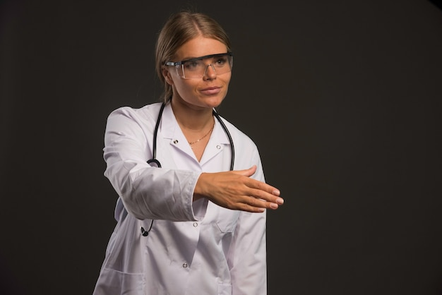 Blonde female doctor with a stethoscope wearing eyeglasses gives hand to someone.