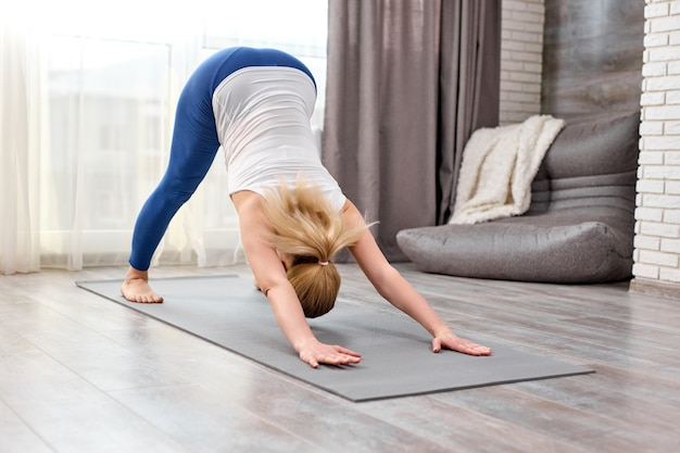 Blonde female doing adho mukha svanasana exercise at home alone Premium Photo