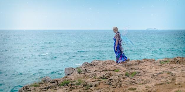 Donna bionda vestita come una fata in piedi sulla riva circondata dal mare sotto un cielo blu