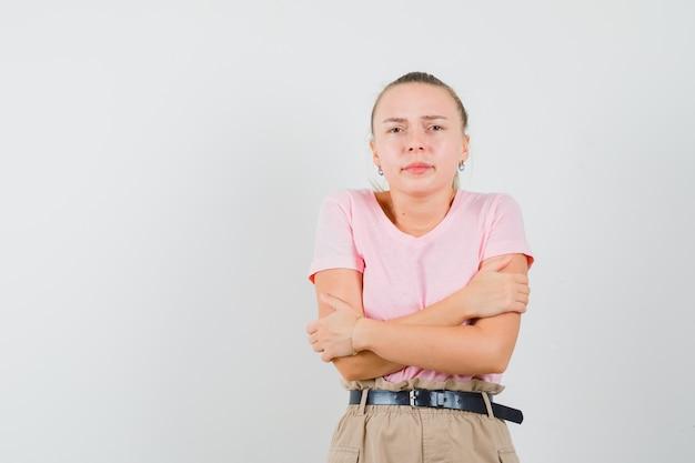 금발 여성은 추위를 느끼고 티셔츠, 바지, 정면도에서 자신을 포옹합니다.